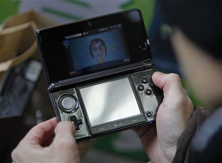 Тойохиса Ишихара (Toyohisa Ishihara), первый покупатель Nintendo 3DS, проверяет свою игровую консоль в Токио