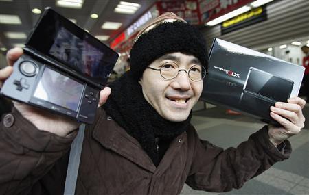 Тойохиса Ишихара (Toyohisa Ishihara), первый покупатель Nintendo 3DS, позирует корреспондентам в магазине электроники в Токио