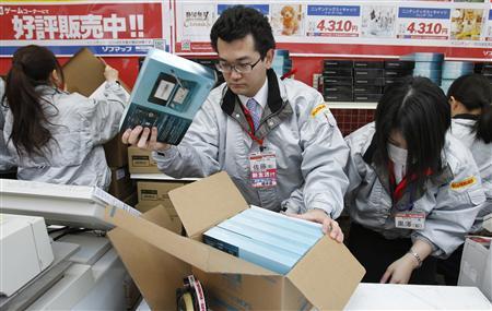 Сотрудники магазина электроники распаковывают новые игровые консоли 3DS во время запуска в Токио