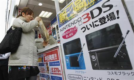 Женщина приобретает Nintendo 3DS в магазине электроники в день запуска