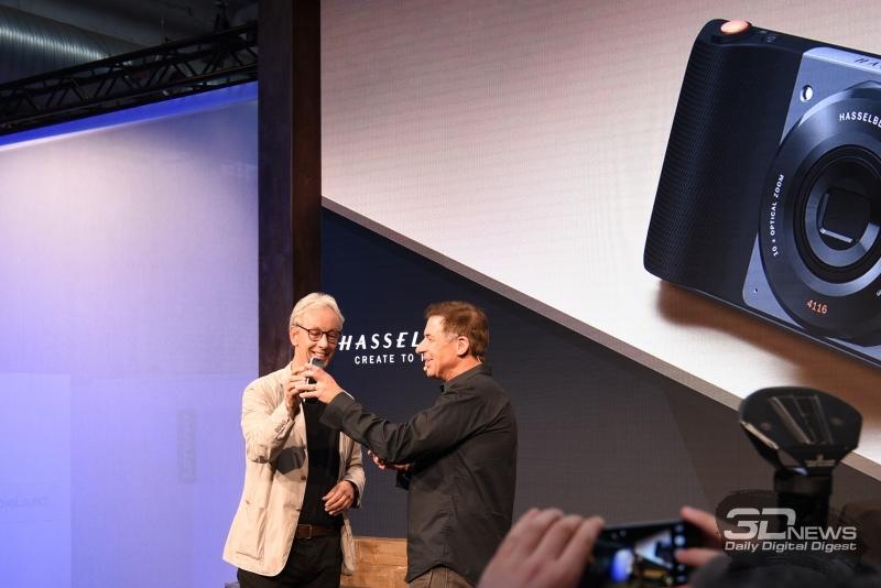 Представители компаний Lenovo и Hasselblad чокаются фотомодулем и смартфоном